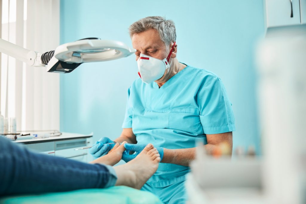 doctor checking feet of diabetic patient