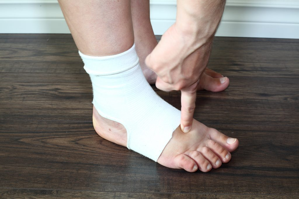hand pointing at foot wearing compression sock